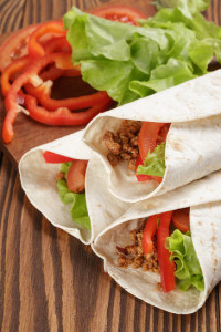 tortilla wraps with beef and vegetables, on wood table